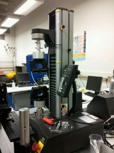 The tensile testing machine utilized to quantify the effectiveness of the artificial microstructures on the BMG to determine tensile ductility. Courtesy of Dr. Baran Sarac.