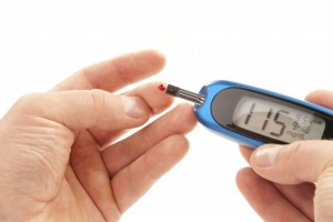 A blood glucose meter being used to test a sample of blood. Reading between 140 and 199 mg/dL indicate glucose intolerance (pre-diabetes) and readings above 200 mg/dL indicate diabetes (type 1 or 2). Image courtesy of completehealthnews.com