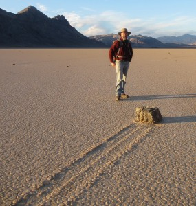 Dr. Richard Norris stands next to one of the sailing stones on Racetrack Playa. The stones only move under the right combination of conditions – thin panels of ice pushing against them as they flow in the direction of the wind. Image courtesy of Richard Norris