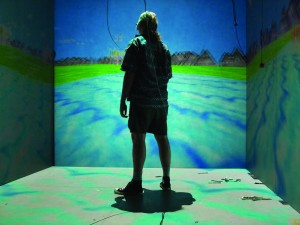 Here, a girl manipulates a cave automatic virtual environment (CAVE). In CAVE, the user resides in a room-sized cube, in which the environment is projected onto three to six of the walls. Image courtesy of Wikipedia.